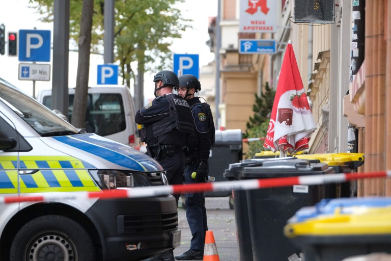 """Policemen secure the area around the site of a shooting in Halle an der Saale, eastern Germany, on October 9, 2019. - At least two people were killed in a shooting on a street in the German city of Halle, police said, adding that the perpetrators were on the run. """"Early indications show that two people were killed in Halle. Several shots were fired. The suspected perpetrators fled in a car,"""" said police on Twitter, urging residents in the area to stay indoors. (Photo by Sebastian Willnow / dpa / AFP) / Germany OUT (Photo by SEBASTIAN WILLNOW/dpa/AFP via Getty Images)"""