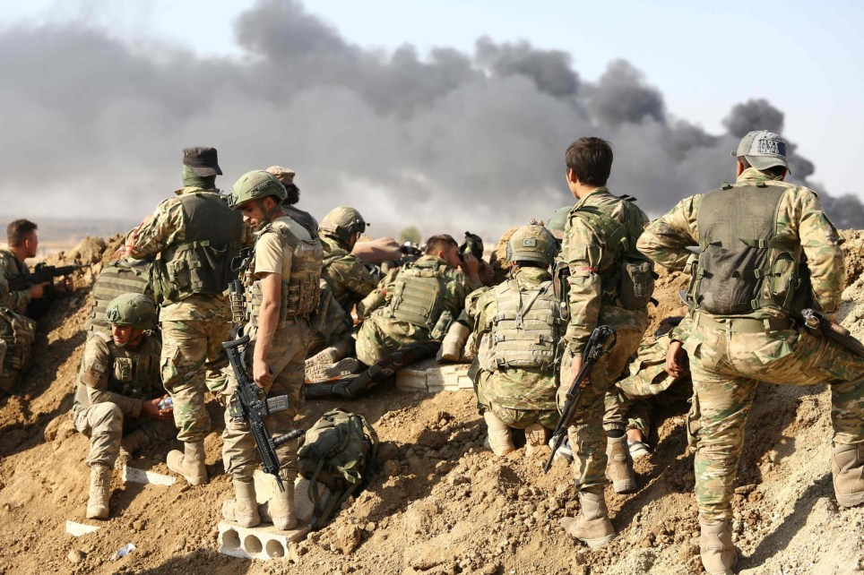 Turkish troops and Turkish-backed Syrian rebels gather outside the border town of Ras al-Ain on October 12, 2019, during their assault on Kurdish-held border towns in northeastern Syria. - Turkey kept up its assault on Kurdish-held border towns in northeastern Syria on Saturday on the fourth day of an offensive that is drawing growing international condemnation, even from Washington. (Photo by Nazeer Al-khatib / AFP) (Photo by NAZEER AL-KHATIB/AFP via Getty Images)