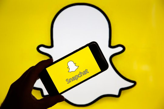 PARIS, FRANCE - APRIL 05: In this photo iIllustration, the Snapchat social media logo is displayed on the screen of an iPhone in front of a computer screen showing a Snapchat logo on April 05, 2019 in Paris, France. During its 'Partner Summit 2019' in Santa Monica, Snapchat has announced several new features to come. Most notable is the ability to send stories to the Tinder dating app. Snapchat is a free photo and video sharing application which has 13 million daily users worldwide. (Photo by Chesnot/Getty Images)