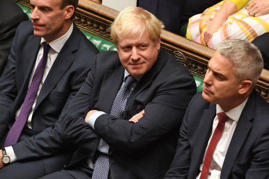 "A handout picture released by the UK Parliament shows Britain's Prime Minister Boris Johnson (C) smiling in the House of Commons in London on October 19, 2019, during a debate on the Brexit deal. - A day of high drama in parliament on Saturday saw lawmakers vote for a last-minute amendment to the deal that could force the government to seek to extend the October 31 deadline to leave. (Photo by JESSICA TAYLOR / UK PARLIAMENT / AFP) / RESTRICTED TO EDITORIAL USE - MANDATORY CREDIT "" AFP PHOTO / UK PARLIAMENT / JESSICA TAYLOR "" - NO USE FOR ENTERTAINMENT, SATIRICAL, MARKETING OR ADVERTISING CAMPAIGNS - EDITORS NOTE THE IMAGE HAS BEEN DIGITALLY ALTERED AT SOURCE TO OBSCURE VISIBLE DOCUMENTS / (Photo by JESSICA TAYLOR/UK PARLIAMENT/AFP via Getty Images)"