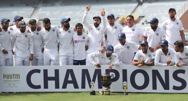 Members of Indian team pose with the winners trophy as captain Virat Kohli, center, flashes victory sign after their win on the fourth day of third and last cricket test match between India and South Africa in Ranchi, India, Tuesday, Oct. 22, 2019. Indian won the series 3-0. (AP Photo/Aijaz Rahi)