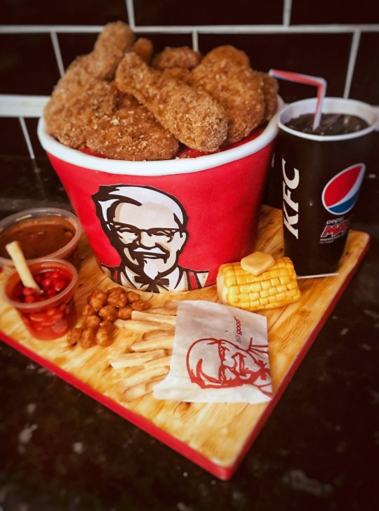 A KFC bucket with chicken wings, beans, gravy, chips and corn with butter - all made from cake