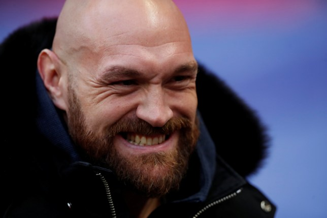 Tyson Fury grins as he poses for pictures on the pitch before an NFL game