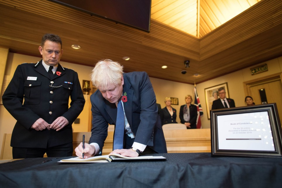 Prime Minister Boris Johnson signs a book of condolence, watched by the Chief Constable of Essex Police, Ben-Julian Harrington, during a visit to Thurrock Council Offices in Essex after the bodies of 39 people were found in a lorry container last week. PA Photo. Picture date: Monday October 28, 2019. See PA story COURTS Container. Photo credit should read: Stefan Rousseau/PA Wire