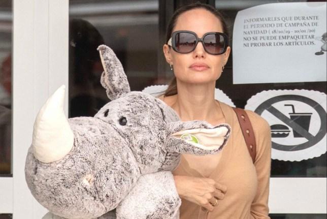 Angelina Jolie carrying a giant Rhinoceros stuffed toy