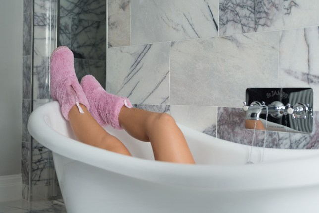 A woman wearing Bedroomathletic slippers in the bath