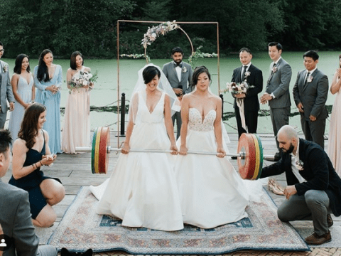 Powerlifting brides celebrate their wedding by deadlifting huge barbell