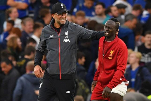 Jurgen Klopp puts his hand around Liverpool forward Sadio Mane