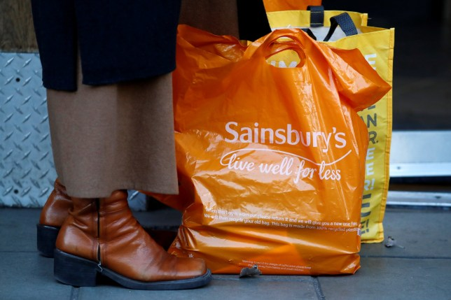 A shopper stands with her purchases in an orange plastic Sainsbury's supermarket store shopping bag in London on November 7, 2019. - Sainsbury's plunged into a net loss in the first half on costly store closures, the British supermarket said Thursday -- and after it recently failed to merge with Walmart-owned Asda. Sainsbury's chalked up a loss after tax of ??38 million ($49 million, 44 million euros) in the 28 weeks to September 21, the retailer said in a trading update. (Photo by Tolga AKMEN / AFP) (Photo by TOLGA AKMEN/AFP via Getty Images)
