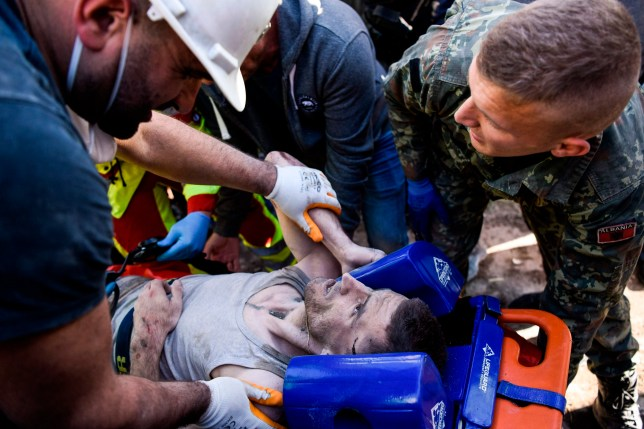 Soldiers and rescue workers carry an injured man found in debris of a collapsed building in Thumane, northwest of capital Tirana, after an earthquake hit Albania, on November 26, 2019. - Albanian rescuers were digging through rubble in search of survivors on November 26, after the strongest earthquake in decades claimed at least 13 lives, with victims trapped in the debris of toppled buildings. The 6.4 magnitude quake struck at 3:54 am local time (0254 GMT), with an epicentre 34 kilometres (about 20 miles) northwest of the capital Tirana in the Adriatic Sea, according to the European-Mediterranean Seismological Centre. (Photo by Armend NIMANI / AFP) (Photo by ARMEND NIMANI/AFP via Getty Images)