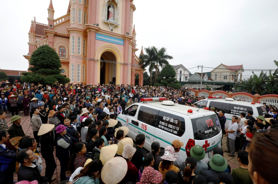 Ambulances carrying the bodies of John Hoang Van Tiep and John Nguyen Van Hung, are being surrounded by relatives and villagers, two victims of 39 deaths on a truck container in UK, in front of a church at homeland in Nghe An province, Vietnam November 27, 2019. REUTERS/Kham