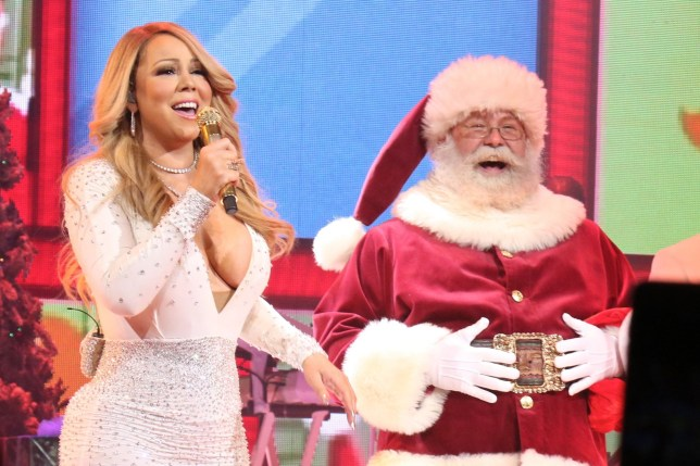 Mariah Carey and Santa while she performs 'All I Want for Christmas Is You' in concert