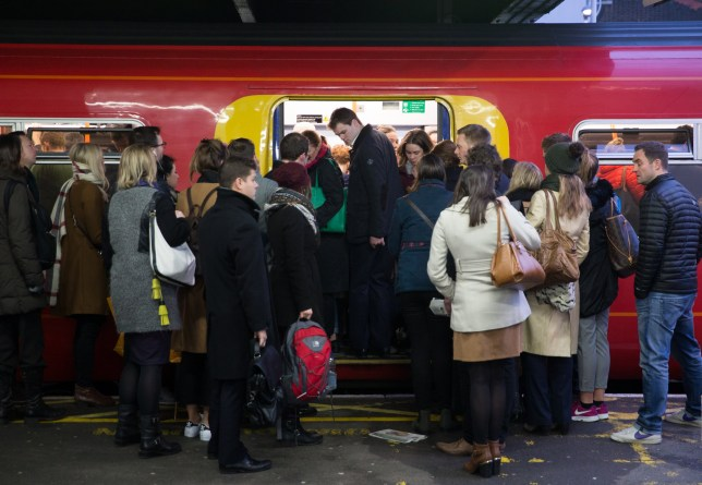 Commuters attempt to board a full Southwest Train carriage toward central London at Clapham Junction station in London on January 10, 2017 after strike action by Southern Rail caused another morning of travel disruption in the British captial. Commuters heading into London were hit by another strike on Southern rail, which caused virtually all services between the southern English coast and the capital to be cancelled. The strike, which has the backing of opposition Labour leader Jeremy Corbyn, will continue into Wednesday and resume on Friday, while further action is also planned for three days later in the month. / AFP / Daniel LEAL-OLIVAS (Photo credit should read DANIEL LEAL-OLIVAS/AFP via Getty Images)