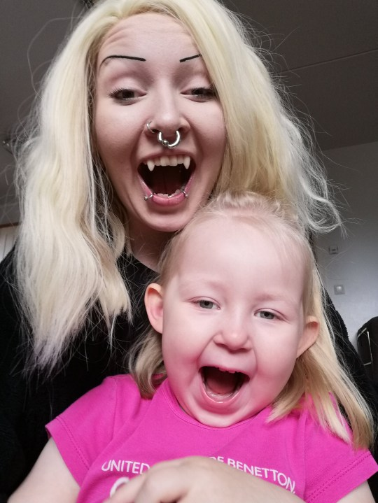 Julia pictured with her daughter showing her fangs. KOTKA, FINLAND: THIS WOMAN spent years researching how to become a REAL-LIFE VAMPIRE before finally getting PERMANENT FANGS FITTED and now says she can SMELL BLOOD from a distance and LOVES THE TASTE ? but don?t worry, SHE ?WON?T BITE?. In 2010, mum of one, Julia Kumpulainen (24) from Kotka, Finland, became fascinated with the vampire lifestyle as she felt she had mutual personality traits as movie vampires. She discovered a company that made temporary costume fangs which she would use daily for the next five years, despite having jaw pain and struggling to eat with them. However, in January 2019, she found a cosmetic dentist who made specialised fangs for her teeth that became a permanent feature which costed her over ?430 (?500). She has since received various reactions from strangers with some even asking her to bite them with her fangs. Despite the social perception of vampires, she wants to change the views that all vampires suck blood from people. She can detect the smell of blood and likes the taste, but would never cut herself to drink it, but if she has a blood-exposing would, she would drink it. Julia, who is a mum to Elli (4), says that her daughter loves her fangs and some people even mistake her for a real vampire and run away in fear. MDWfeatures / Julia Kumpulainen