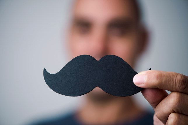 closeup of a young man holding a fake moustache in front of his face