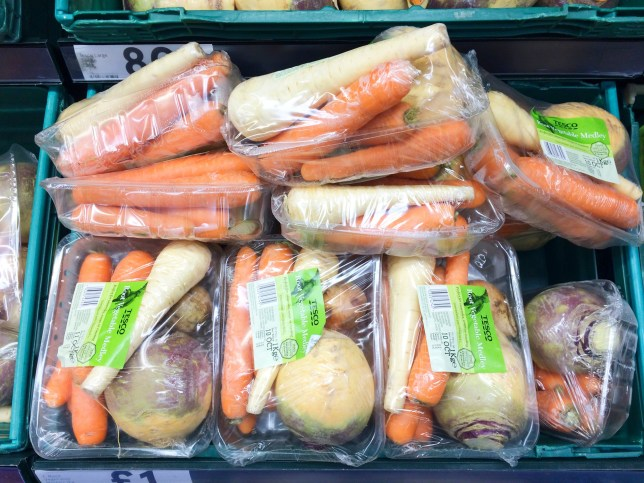 Europe UK Bedfordshire Bedford 9th October 2018. Major supermarket. Green crate of vegetables in food aisle. Mixed carrots parsnips and swede. Plastic wrapping on produce. ; Shutterstock ID 1203544396; Purchase Order: -