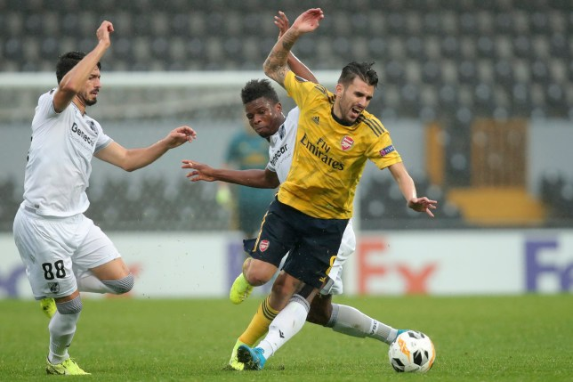 Arsenal's Dani Ceballos is fouled by Vitoria's Mikel Agu, background, during the Europa League group F soccer match between Vitoria SC and Arsenal at the D. Afonso Henriques stadium in Guimaraes, Portugal, Wednesday, Nov. 6, 2019. (AP Photo/Luis Vieira)