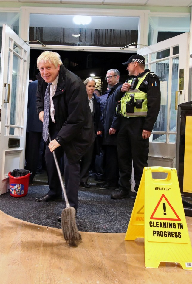 Britain's Prime Minister Boris Johnson mops the floor to help with the clean-up at an opticians during a visit to the flood-hit town of Matlock, Derbyshire, Britain November 8, 2019. Picture taken November 8, 2019. Danny Lawson/Pool via REUTERS