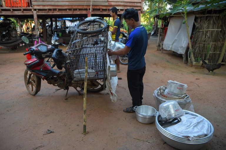 This photo taken on October 25, 2019 shows men loading pans, which will be exchanged with dogs, onto his motorcycle at a slaughterhouse in Siem Reap province. - Cambodian dog meat traders drown, strangle and stab thousands of canines a day in a shadowy but sprawling business that traumatises workers and exposes them to deadly health risks like rabies. (Photo by TANG CHHIN Sothy / AFP) / TO GO WITH Cambodia-animal-dog-food, FEATURE by Joe FREEMAN and Suy SE (Photo by TANG CHHIN SOTHY/AFP via Getty Images)