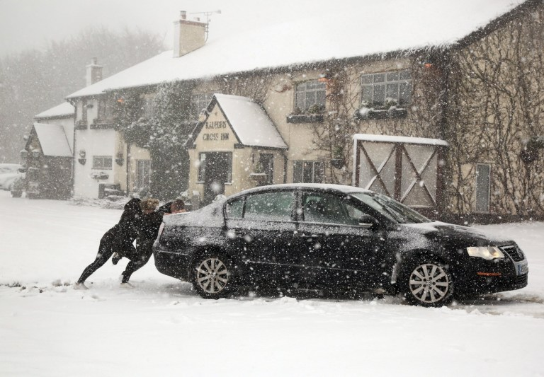 Heavy snow makes roads on Exmoor Impassable on Thursday - A car is pushed along the B3224 at Raleighs Cross on Exmoor this morning. November 14, 2019.