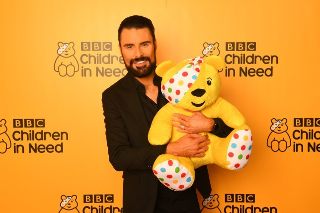 Rylan Clark-Neal posing with Pudsey bear in front of a BBC Children in Need 2019 logo