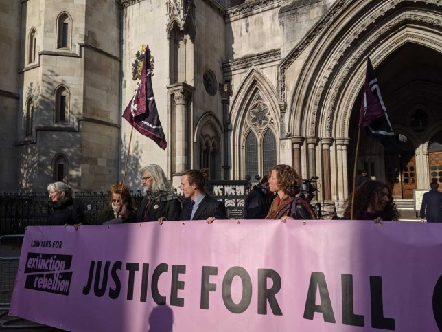 People standing outside the High Court holding a sign that says 'Lawyers for Extinction Rebellion: Justice For All'