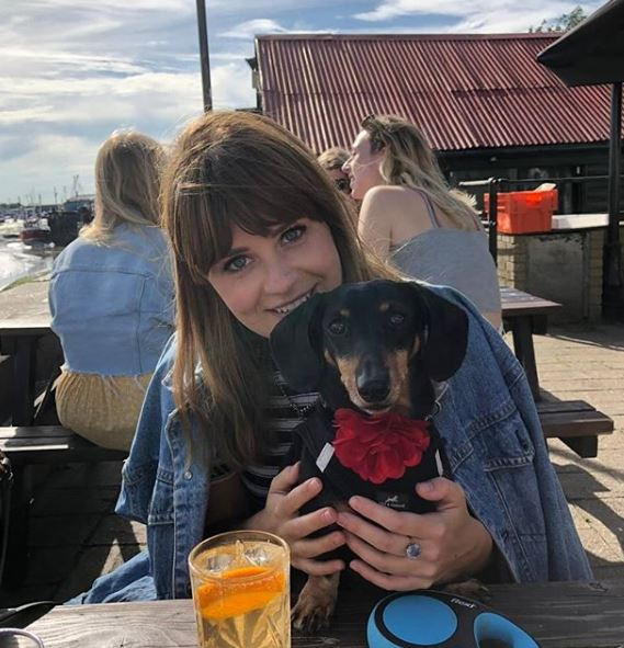 Hana Carter holds a very cute dog on her lap