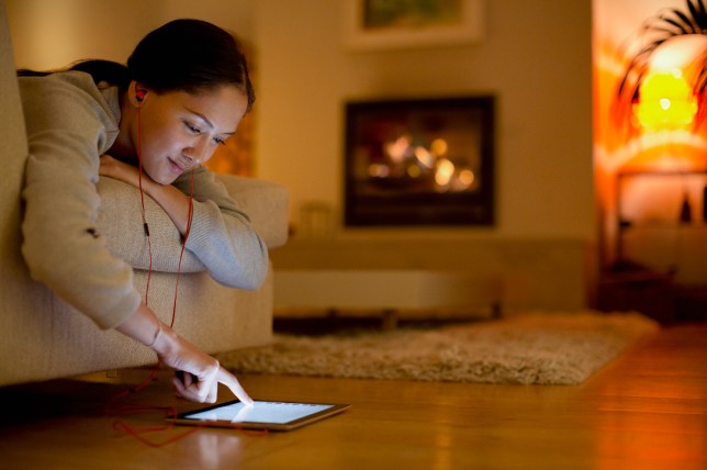 Young woman with headphones using digital tablet in living room.