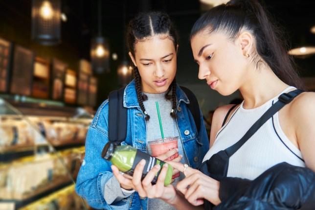 Two people examining ingredient list on juice bottle