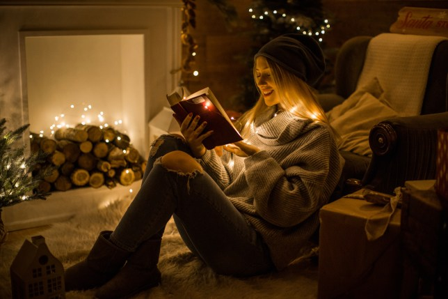 woman reading a book in front of the fire