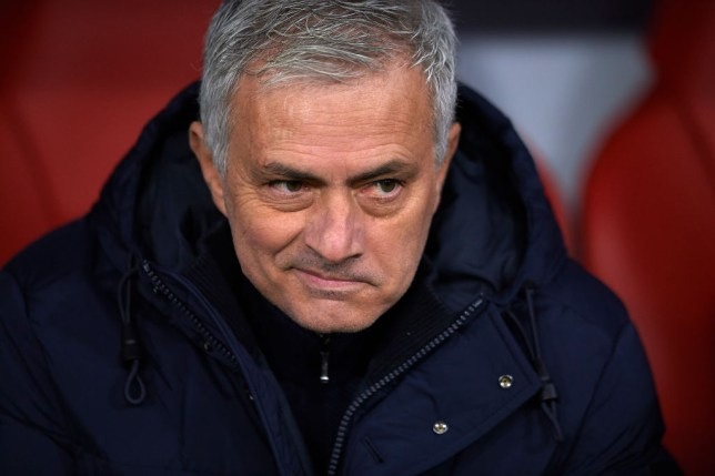 Jose Mourinho smirks as he sits on the Tottenham bench during a game