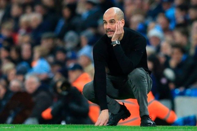 Pep Guardiola crouches on the ground during a Manchester City game