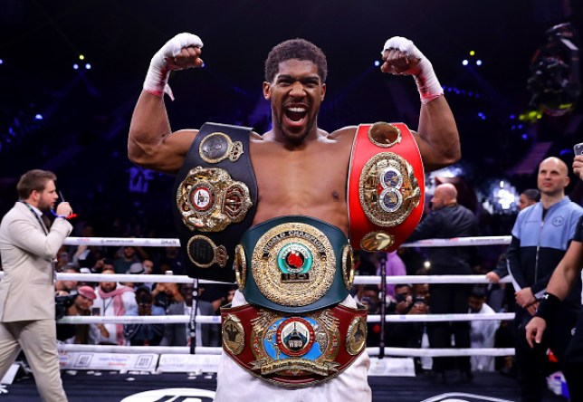 Anthony Joshua poses with all his heavyweight titles