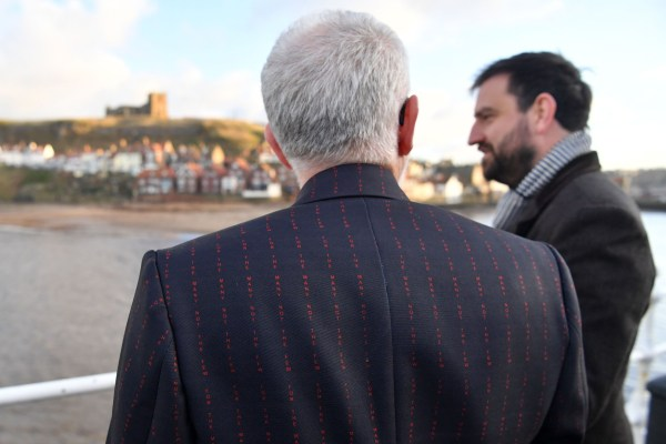 "Prospective parliamentary candidate for Scarborough and Whitby, Hugo Fearnley (R) and ppposition Labour Party leader Jeremy Corbyn wearing a jacket with their slogan ""For The Many Not The Few"" sown into the cloth, campaign in Whitby, northern England, on December 1, 2019 during a general election campaign visit. - Britain will go to the polls on December 12, 2019 to vote in a pre-Christmas general election. (Photo by Paul ELLIS / AFP) (Photo by PAUL ELLIS/AFP via Getty Images)"