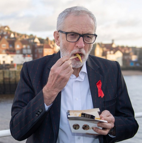 "Labour leader Jeremy Corbyn eats chips in Whitby, while on the General Election campaign trail, wearing a jacket that has ""for the many not the few"" printed all over it. PA Photo. Picture date: Sunday December 1, 2019. See PA story POLITICS Election. Photo credit should read: Joe Giddens/PA Wire"
