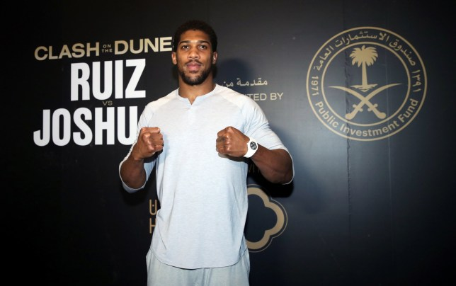 Heavyweight boxer Anthony Joshua poses for pictures as he arrives in Saudi Arabia