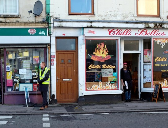 "A teacher (left) stands outside Chilli Bellies while owner Neil D'Souza looks. See SWNS story SWBRtakeaway A takeaway owner called the police after claims that two teachers were acting like BOUNCERS outside his shop - and giving detentions to any who refused to leave. Neil D'Souza, owner of Chilli Bellies in Bristol, says he has seen a massive drop in business since staff from Cotham School started patrolling the streets. The school has a policy of policing nearby roads after the end of the day at 2:45pm - and has banned students from entering various businesses before 3:15pm. Officers were called by Mr D'Souza last week when staff allegedly blocked the entrance to his shop and stepped in to boot pupils out. The school has denied teachers entered the premises at all and insisted teachers were simply making sure pupils got home safely. Mr D'Souza said: ""They came in the shop and started telling off the children who were in there, handing out detentions, demanding that they leave. ""I?d taken the children's money, their food was almost ready. I said I?d had enough and asked this teacher to leave, to get out of my business, get off my property. ""He argued with me, and then went and stood right on the doorstep. He was physically blocking the entrance. ""They were intimidating the students, and this was intimidating to my normal customers too. He refused to move, that?s why I called the police."" Local resident Kate Grant also tried to enter the shop - and also challenged the teachers. She said: ""You?ve got two senior teachers in high-vis jackets standing outside a shop like bouncers. ""This is after school, with the kids on their way home. Young people have a hard enough time as it is."