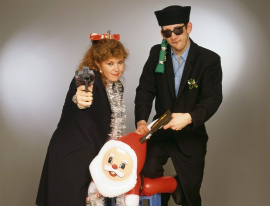 Singers Kirsty MacColl (1959 - 2000) and Shane MacGowan with toy guns and an inflatable Santa in a festive scenario, circa 1987. In 1987, the pair collaborated on the Pogues' Christmas song 'Fairytale of New York'.
