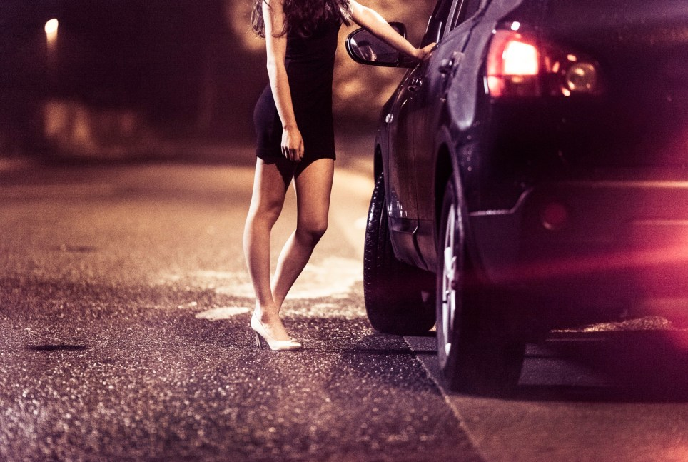 Street prostitute standing by the car