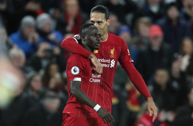 Virgil van Dijk puts his arm around Sadio Mane after a goal for Liverpool
