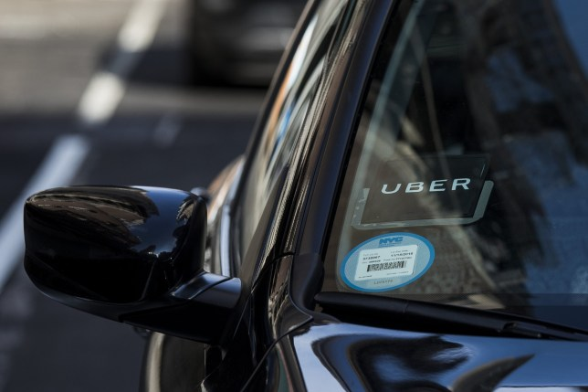 The Uber Technologies Inc. logo is seen on the windshield of a vehicle in New York, U.S., on Thursday, Aug. 9, 2018. New York's city council dealt a political blow to??Uber Technologies Inc.??and other app-based car-for-hire companies by approving a one-year industry wide cap on new licenses and giving the city Taxi & Limousine Commission authority to set minimum pay standards for drivers. Photographer: John Taggart/Bloomberg via Getty Images