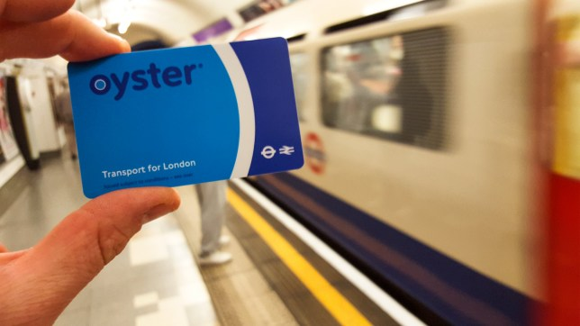 A hand Holding an Oyster Card, with a moving London Underground train in the background.