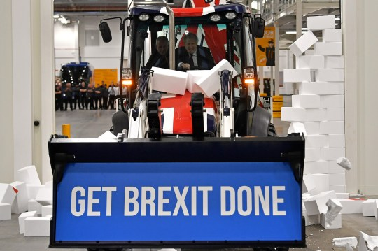 "UTTOXETER, ENGLAND - DECEMBER 10: Britain's Prime Minister and Conservative party leader Boris Johnson drives a Union flag-themed JCB, with the words ""Get Brexit Done"" inside the digger bucket, through a fake wall emblazoned with the word ""GRIDLOCK"", during a general election campaign event at JCB construction company on December 10, 2019 in Uttoxeter, Staffordshire, United Kingdom. The U.K will go to the polls in a general election on December 12. (Photo by Ben Stansall - WPA Pool/Getty Images)"