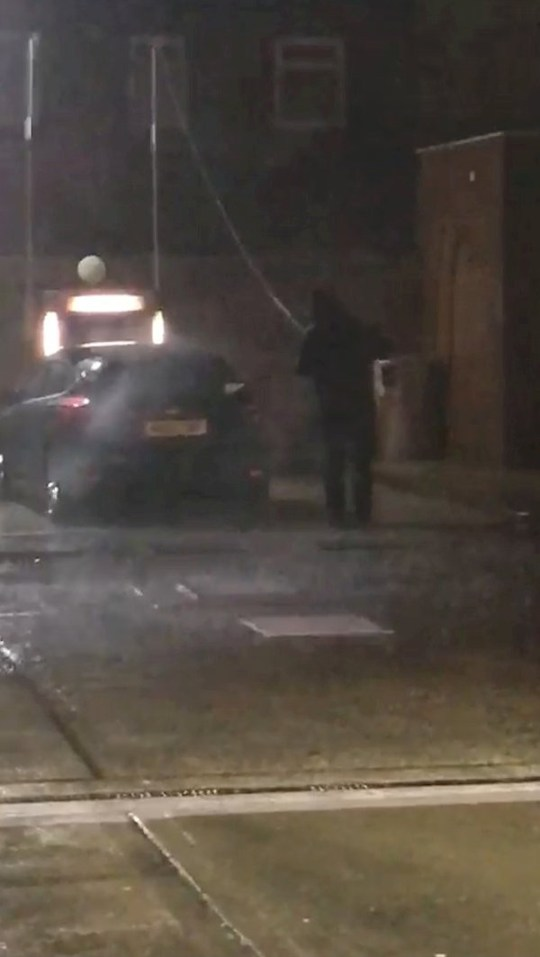 """Video grab from the bizarre moment a man was seen washing his car at Farnworth Filling Station in Bolton, Manchester - in the middle of a massive rain storm! See SWNS story SWOCrain. This is the hilarious moment a guy was spotted washing his car in a petrol station - during the middle of a heavy STORM. Video shows a man wearing a hoodie battling the elements, washing his car as rain lashes down, at Farnworth Filling Station in Bolton, Manchester. He was filmed by Jack Rowson, 29, who couldn't believe his eyes. He can be heard saying in the video: """"Right, check this out, check the weather!"""