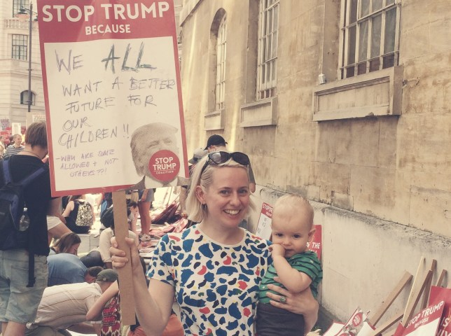 Franki Cookney with her son Sacha, holding up a placard at a Stop Trump rally