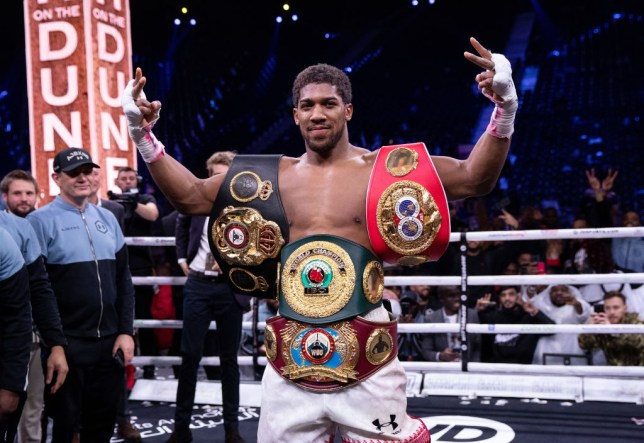 Anthony Joshua poses with all his heavyweight belts