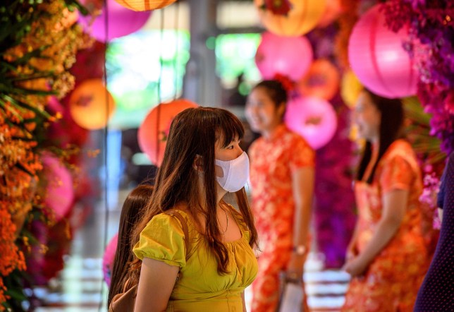 a woman in a face mask walked around bangkok thailand