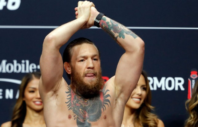 Conor McGregor raises his hand to acknowledge UFC fans