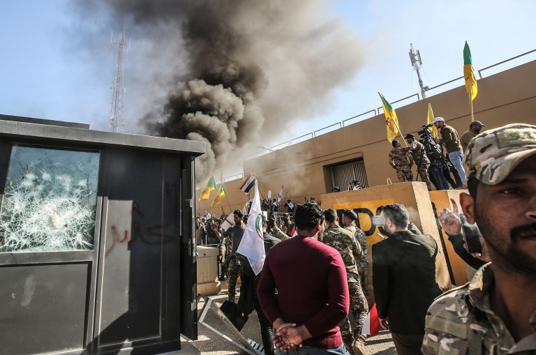 """Members of the Iraqi pro-Iranian Hashed al-Shaabi group and protesters set ablaze a sentry box in front of the US embassy building in the capital Baghdad to protest against the weekend's air strikes by US planes on several bases belonging to the Hezbollah brigades near Al-Qaim, an Iraqi district bordering Syria, on December 31, 2019. - Several thousand Iraqi protesters attacked the US embassy in Baghdad on today, breaching its outer wall and chanting """"Death to America!"""" in anger over weekend air strikes that killed pro-Iran fighters. (Photo by Ahmad AL-RUBAYE / AFP) (Photo by AHMAD AL-RUBAYE/AFP via Getty Images)"""