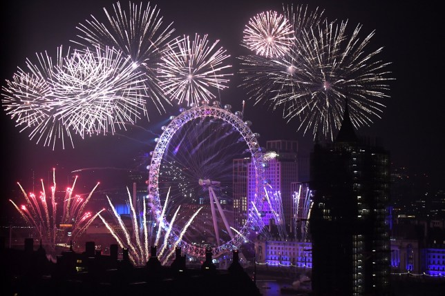 LONDON, ENGLAND - JANUARY 1: Fireworks explode over The Coca-Cola London Eye, Westminster Abbey and Elizabeth Tower near Parliament as thousands of revelers gather along the banks of the River Thames to ring in the New Year on January 1, 2019 in London, England. At the stroke of midnight, Big Ben rang in the new decade after being silent all year long for renovations. (Photo by Chris J Ratcliffe/Getty Images)